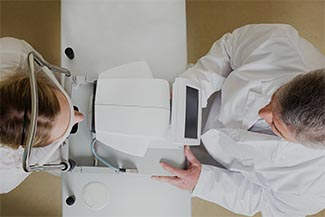 Eye care, patient receiving eye exam with Auto-refractor in Akron, OH