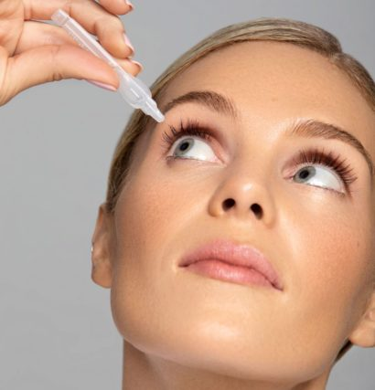 woman putting on an eye drop