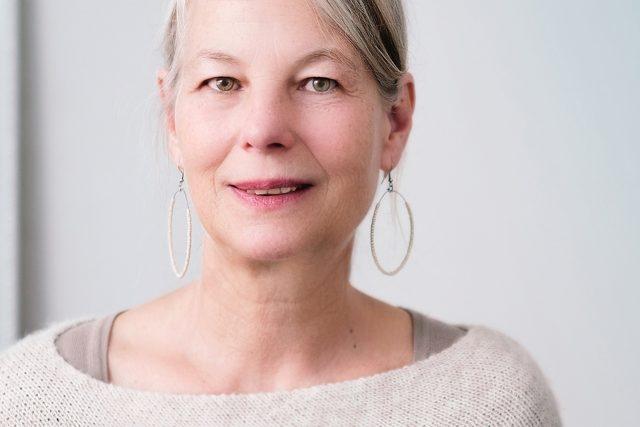 optometrist, older woman with hoop earings, wearing scleral lenses in Fair Lawn, NJ